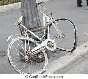 white bicycle abandoned on a light pole