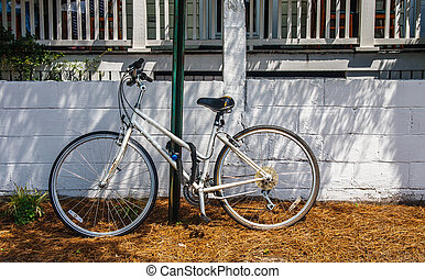 Old White Bicycle Chained to Green Pole
