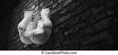 Old white boxing gloves hang on nail on brick wall with copy space for text. High resolution 3d render