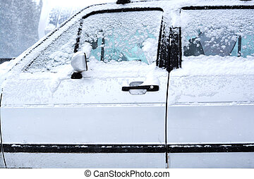 Old white car covered by snow in wintertime