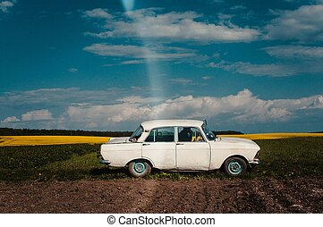 Old white car parked on the field in summer day. Ukrainian car.