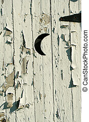 Old white outhouse moon door