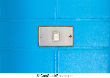 Old white switch on the bue wall