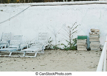 Old white vintage wooden sun loungers standing near the wall at the beach after the end of a summen season.