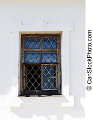 Old white wall of castle prison with a window with bars from...