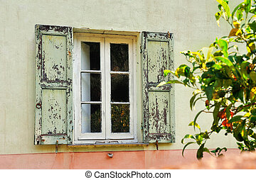 Old white window with light green shutters