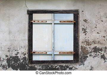 Old white wooden shutter windows with closed doors on a dirty wall