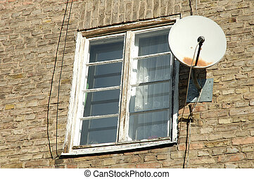Old white wooden window and satellite dish