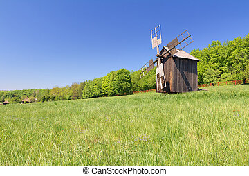 Old wind mill on a spring meadow with blue sky
