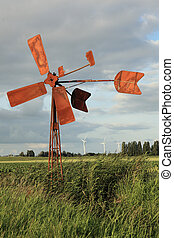 old wind mill with modern wind turbines - Broken and rusty...