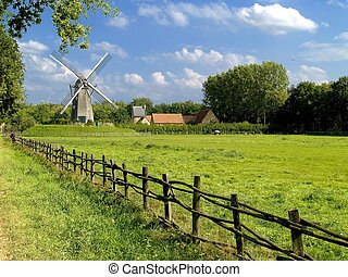 Old windmill, blue cloudy sky. - Old windmill against a blue...