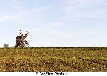Old windmill by a farmers corn field