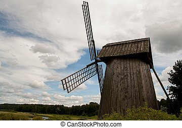 old windmill in a field near the river
