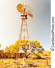 Old windmill water pump in dry landscape. Metallic tower...