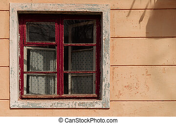 Old window in abandoned house with wooden red frame and curtain