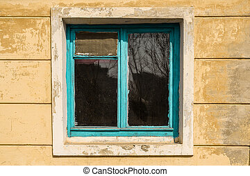 Old window in an abandoned house with blue wooden frame