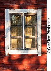Old window in red wooden house