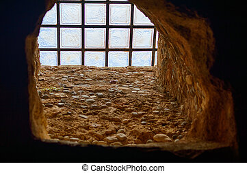 old window in the building with cross bars on the window to avoid unwelcome intrusion.