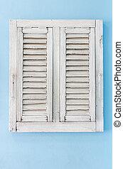 Old window on blue sky wall