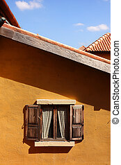 Old window on orange wall