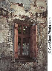 Old window on the broken wall