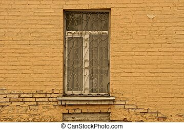 old window with an iron grill on a brick brown wall