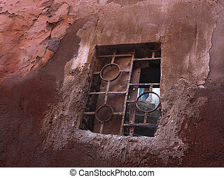 Old window with ancient metal grate on a red wall in the medina of Marrakesh, Morocco.