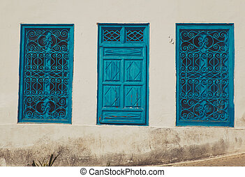 Old window with blue shutters on dirty white wall
