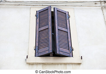 Old window with closed shutters on the window sill on the ...