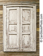 old window with shutters on a wooden wall