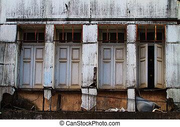 Old windows on ruin house