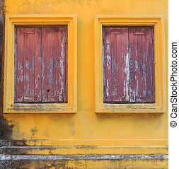 Old windows on yellow wall