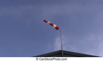 old windsock in airfield showing wind strength on blue sky