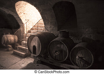 Old wine cellar with wooden barrels and stone stairs