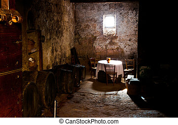 Old cellar lit basement of a small window with table and chairs for wine pitcher hit by the ray of sunshine piercing the darkness