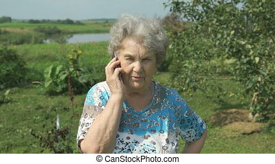 Old woman 80s telling on the smartphone outdoors