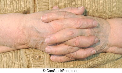 Old woman aged 80s makes massages their of hands. Close up