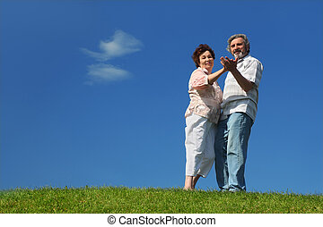 old woman and man dancing on summer lawn, blue sky