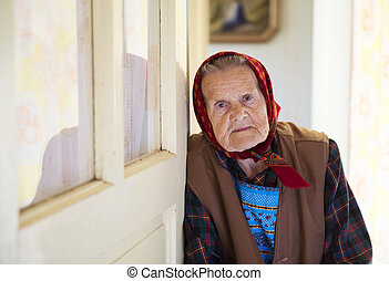 Old woman at home - Very old woman is standing by the door...