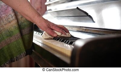 Old woman at home wipes the dust on piano, close up