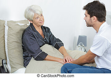 old woman at hospital ward with assistant