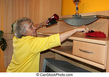 Old woman cleans a cupboard, cleans it from the dust.