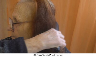 Old Woman Combing Her Hair At Home