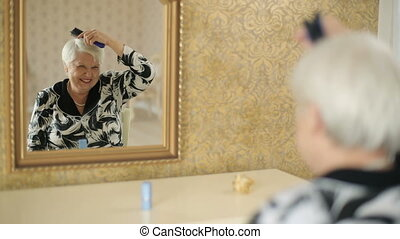 Portrait of smiling senior woman styling her hair in a fron of the mirror