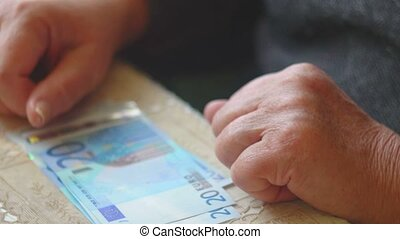 Old woman counting euro banknotes closeup, selective focus