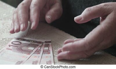 Old woman counting euro banknotes, vintage toned image