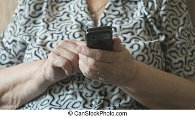 Old woman dials the number on mobile phone