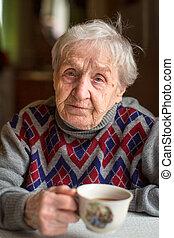 Old woman drinking tea.