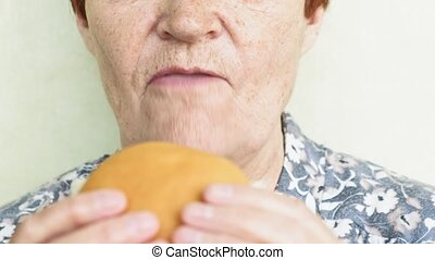 old woman eating burger closeup, fast food - old woman with...