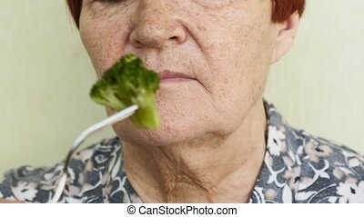 old woman eating choices eating vegetables or chicken